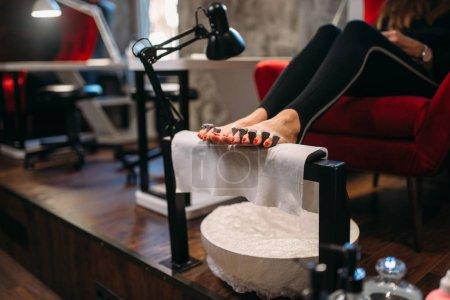 Photo pour Femme cliente en procédure cosmétique pédicure dans un salon de beauté. Soins professionnels des ongles et de la peau des pieds - image libre de droit