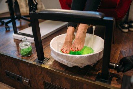 Photo pour Pieds de cliente dans un bain de pédicure, vue de dessus, procédure cosmétique dans le salon de manucure. Soins professionnels des ongles et de la peau des pieds - image libre de droit
