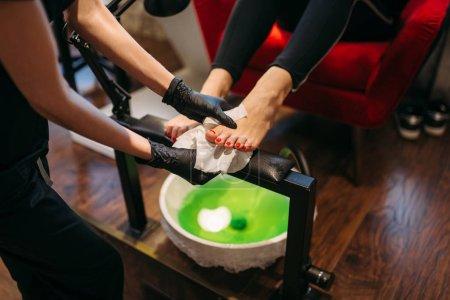 Photo pour Master de pédicure en gants noirs faire procédure cosmétique, clientes dans un salon de beauté. Soin des ongles professionnel - image libre de droit
