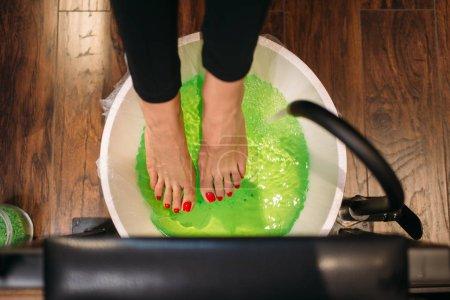 Photo pour Pieds de clientes dans un bain de pédicure, la vue de dessus, la procédure cosmétique en salon de manucure. Soins de la peau professionnel ongle et du pied - image libre de droit