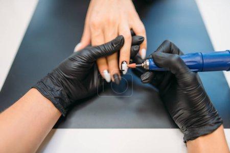 Photo pour Esthéticienne dans gants détient polisseuse et nettoie les vieux vernis des ongles des clientes, vue de dessus, manucure dans un salon de beauté. Manucure fait mains soin procédure cosmétique - image libre de droit
