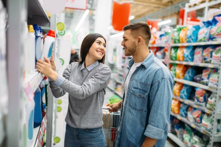 Photo for Couple in department of household chemicals, goods on shelves in supermarket, family shopping. Customers in shop, buyers in market - Royalty Free Image