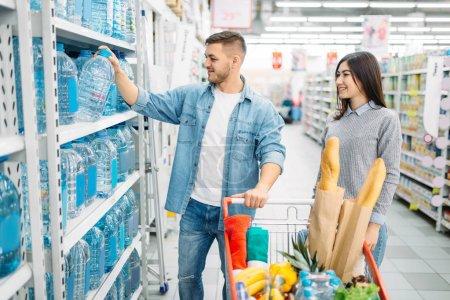 Photo pour Jeune couple avec chariot prend cartouche d'eau du plateau dans un supermarché, boutiques familiales. Clients en magasin, les acheteurs dans le marché, Département des marchandises pour les enfants - image libre de droit