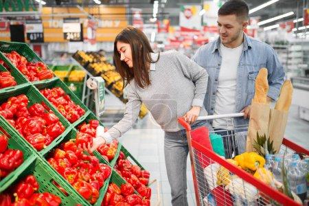 Photo pour En couple avec panier choisir frais poivrons rouges dans un supermarché, boutiques familiales. Clients dans la boutique, les acheteurs dans le marché - image libre de droit
