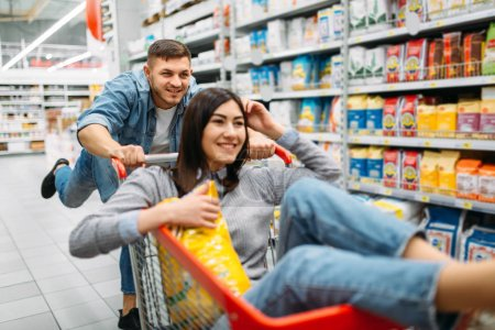Husband carries his wife in the cart in supermarke...
