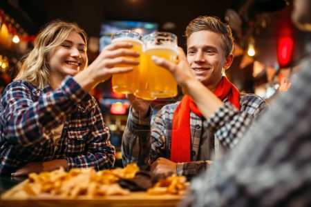 Photo for Football fans drinks beer at the table in sports bar. Victory celebration, tv broadcasting, young friends leisures in pub - Royalty Free Image