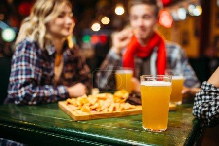 Foto de Amigos felices viendo partido y bebiendo cerveza en el bar de deportes - Imagen libre de derechos