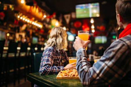 Photo for Happy friends watching match and drinking beer in sports bar - Royalty Free Image