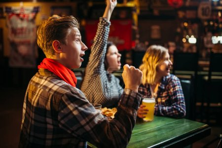 Photo for Football fans watching match and rejoice scored a goal in sports bar. Tv broadcasting, young friends leisures in pub - Royalty Free Image