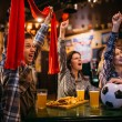 Football fans with scarf watching match and raise ...