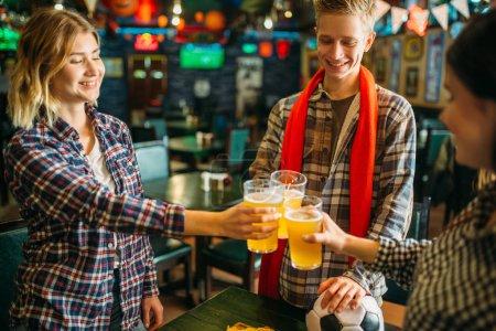 Photo pour Les fans de football joyeux lèvent leur verre à bière légère au bar des sports. Télédiffusion, jeunes amis célèbre la victoire de l'équipe favorite, célébration jeu succès dans pub - image libre de droit