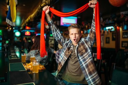 Photo for Young football fan with scarf raises his hands up at the counter in sports bar. Tv broadcasting, teenager watching the match of the favorite team, success game celebration in pub - Royalty Free Image