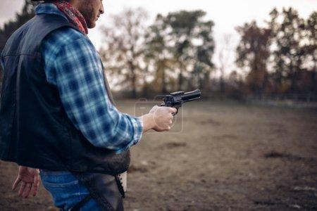 Photo pour Cowboy avec revolver, vue de face, fusillade sur le ranch au texas, l'Ouest. Personne de sexe masculin vintage avec pistolet, far west aventure - image libre de droit
