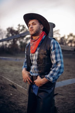 Photo pour Jeune cowboy en veste de cuir et chapeau pose contre corral de cheval, Ouest. Personne de sexe masculin vintage, rétro mode américaine dans le style far west - image libre de droit