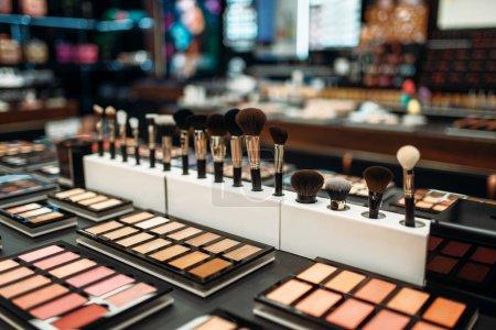 Photo pour Face collection cosmétique en beauté magasin agrandi, personne. Produits de maquillage en boutique, poudres et pinceaux - image libre de droit