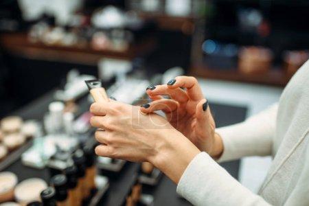 Photo pour Client féminin testant la crème de fond de teint dans la boutique de maquillage. Cosmétiques au choix en boutique de beauté, salon de maquillage - image libre de droit