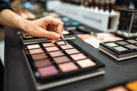 Photo for Female hand with brush, powder testing, showcase in the makeup shop. Cosmetics choosing in beauty store, make-up salon - Royalty Free Image