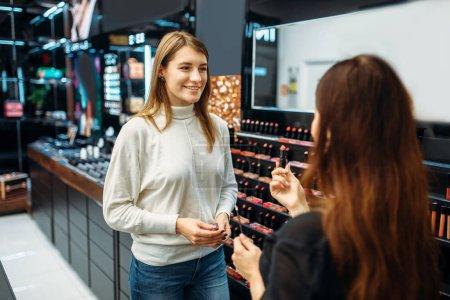 Photo pour Consultant vendeur et cliente dans la boutique de maquillage. Choix de cosmétiques en magasin de beauté - image libre de droit