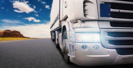 Photo for Cargo truck speeding on highway at sundown - Royalty Free Image
