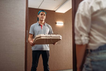 Photo for Pizza delivery boy with carton box in hands on the doorstep, delivering service. Courier from pizzeria and customer indoors - Royalty Free Image
