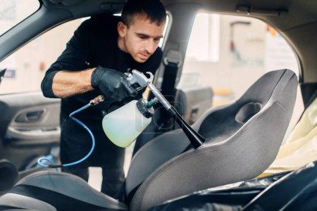 Nettoyage professionnel à sec des sièges d'auto. Service de lavage de voiture, travailleur masculin utilisant pulvérisation