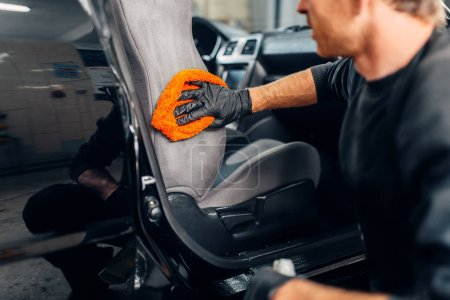 Photo for Chemical cleaning of car seats using special agent. Carwash service, male worker in gloves removes dirt - Royalty Free Image