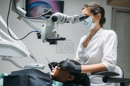 Photo pour Dentiste fait une chirurgie pour femme, visite en clinique dentaire. Patiente en cabinet de dentisterie, stomatologie, soins des dents - image libre de droit