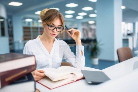 Photo pour Jolie femme en lunettes apprenant le livre à la bibliothèque. Femme dans la salle de lecture, dépôt de connaissances - image libre de droit