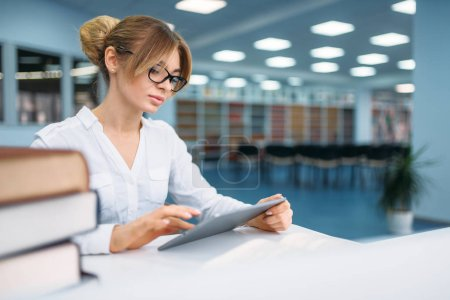 Photo for Pretty female student sitting in library. Young woman in reading room, knowledge depository - Royalty Free Image