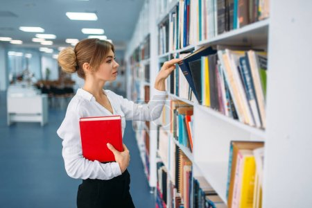 Young woman looking book at the shelf in library. Female person in reading room, knowledge depository