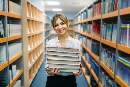 Photo pour Personne assez féminine avec pile de livres entre les étagères de la bibliothèque de l'université. Jeune femme en salle de lecture, dépositaire de la connaissance - image libre de droit