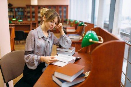 Photo pour Livre de lecture de jolie jeune femme à la table dans la bibliothèque de l'université. Personne du sexe féminin au dépositaire de la connaissance - image libre de droit