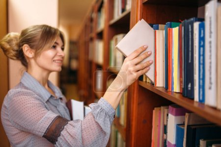 Photo for Young woman takes book from shelf in university library. Female person in knowledge depository - Royalty Free Image