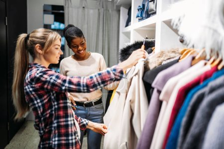 Photo for Two girlfriends choosing clothes, shopping. Shopaholics in clothing store, consumerism lifestyle, fashion - Royalty Free Image
