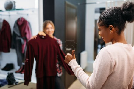Photo for Two women choosing clothes, shopping. Shopaholics in clothing store, consumerism lifestyle, fashion - Royalty Free Image
