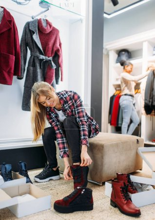 Photo for Two girlfriends buying clothes and shoes, shopping. Shopaholics in clothing store, consumerism lifestyle, fashion - Royalty Free Image