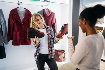 Photo for Two females buying clothes and shoes, shopping. Shopaholics in clothing store, consumerism lifestyle, fashion - Royalty Free Image