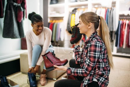 Photo for Two female friends trying on shoes, shopping. Shopaholics in clothing store, consumerism lifestyle - Royalty Free Image