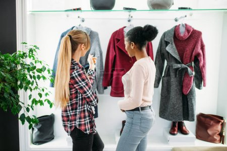 Photo for Two girlfriends looking at the coat in shop, shopping. Shopaholics in clothing store, consumerism lifestyle, fashion - Royalty Free Image