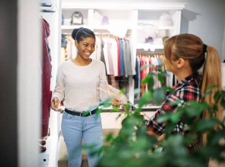 Photo for Two female friends choosing coats in shop, shopping. Shopaholics in clothing store, consumerism lifestyle - Royalty Free Image