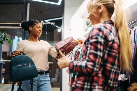 Photo for Two females choosing bags in shop, shopping. Shopaholics in clothing store, consumerism lifestyle, fashion - Royalty Free Image