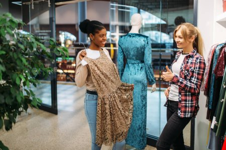 Photo for Two female friends choosing dresses in shop, shopping. Shopaholics in clothing store, consumerism lifestyle, fashion - Royalty Free Image
