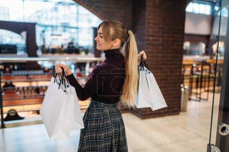 Photo pour Jeune femme avec des sacs à provisions dans le centre commercial. Commerçant dans le magasin de vêtements, mode de vie consumérisme, mode, achat de dame attrayante dans le magasin - image libre de droit
