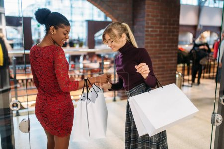 Two female customers with shopping bags in mall. Shopaholics in clothing store, purchasing, fashion