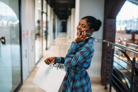 Photo for Black female person with phone and shopping bags in mall. Shopaholic in clothing store, consumerism lifestyle, fashion - Royalty Free Image