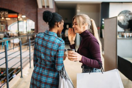 Photo for Two young attractive women with shopping bags in mall. Shopaholics in clothing store, purchasing, female buyers in shop - Royalty Free Image