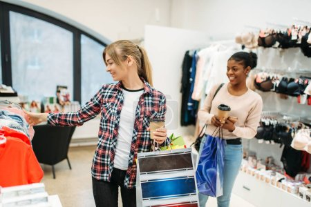 Photo for Two young attractive women shopping, ladies lingerie. Shopaholics in clothing store, consumerism lifestyle, fashion, female shoppers with bags - Royalty Free Image