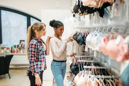 Photo for Two women against showcase with underwear, shopping. Shopaholics in clothing store, consumerism lifestyle, fashion, female shoppers in lingerie section - Royalty Free Image