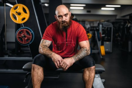 Strong athlete sitting on the bench, workout in gym. Bearded sportsman on training in sport club, healthy lifestyle