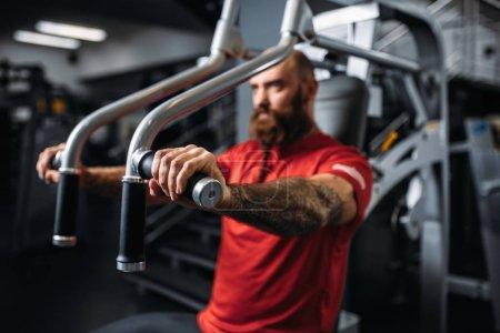 Photo pour Athlète musclé sur machine d'exercice dans la salle de gym. Homme barbu sur la séance d'entraînement au club de sport - image libre de droit